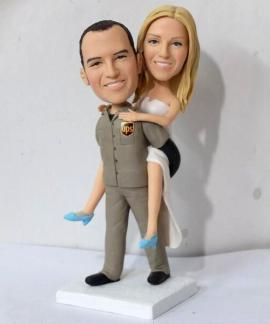 Custom UPS groom carring his bride cake topper