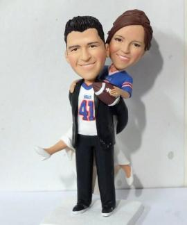 Groom carring the bride football theme cake topper